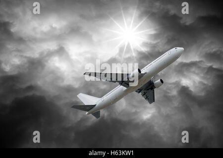 Flugzeug unter Sonne, die von dunklen Wolken des stürmischen Himmel leuchtet - Stockfoto