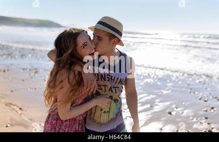 Glückliches junges Paar in Liebe zu Fuß am Strand entlang - Stockfoto