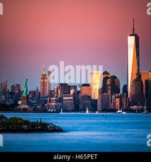 Lower Manhattan bei Sonnenuntergang. Der Freedom Tower, One World Trade Center, Empire State Building und die Freiheitsstatue - Stockfoto