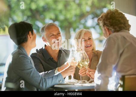 Paare, die Weißweingläser an sonnigen Restauranttisch Toasten - Stockfoto