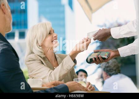 Geschäftsfrau, die Kellner mit Credit Card Reader an städtischen Straßencafé zu bezahlen - Stockfoto