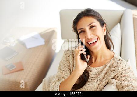 Lachende Frau am Handy auf sofa - Stockfoto