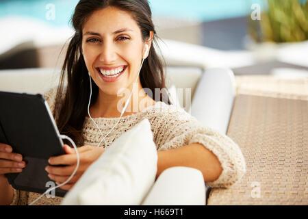 Porträt lächelnde Frau mit digital-Tablette und Kopfhörer auf sofa - Stockfoto