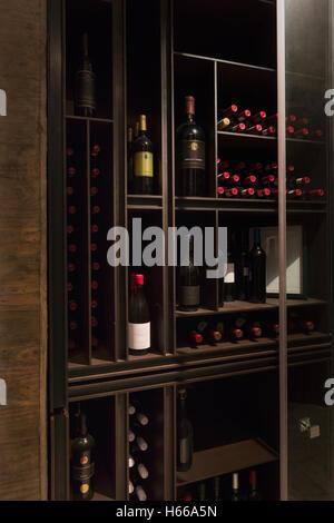 Weinflaschen auf Holzregalen in Wein-Bibliothek organisiert - Stockfoto