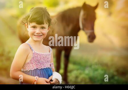 Fünf Jahre altes Landmädchen spielen in der Nähe von ihrem Pferd. - Stockfoto