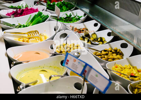 Eine Auswahl an Oliven, Chili, Saucen und Beilagen am Buffet Schalter eines Restaurants - Stockfoto