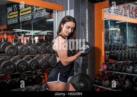 Frau tut Bizeps locken in ein Fitness-Studio - Stockfoto
