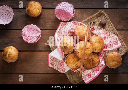 Obst-Muffins mit Muskat und Piment in einem Weidenkorb auf einem hölzernen Hintergrund. Ansicht von oben - Stockfoto
