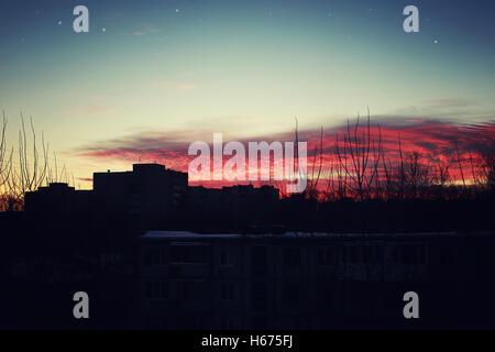 roter Sonnenuntergang Himmel Silhouetten von Gebäuden - Stockfoto