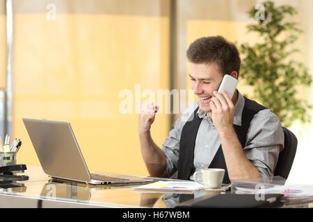 Aufgeregt Geschäftsmann telefonieren mit Handy während beobachtet Unternehmensinhalte in einem laptop - Stockfoto