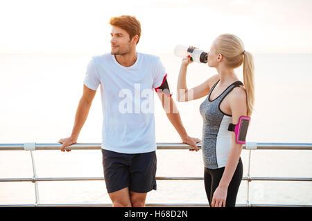 Junge Fitness Mann und Frau ruht nach dem Joggen an der pier - Stockfoto