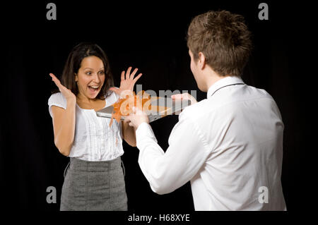Business-Frau, die einen Laptop von einem Geschäftsmann gegeben - Stockfoto