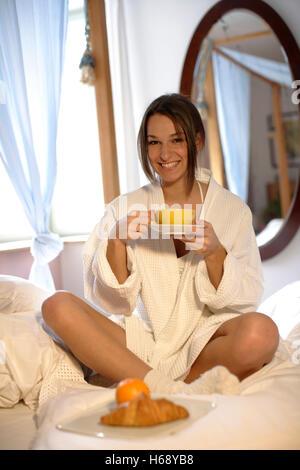 Frau im Bett zu frühstücken - Stockfoto
