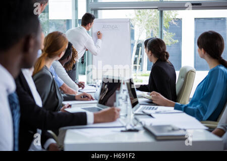 Geschäftsmann am Whiteboard mit Kollegen diskutieren - Stockfoto