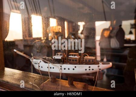 Ein Holzmodell der S.Y Sea Cloud, gesehen durch die Fenster der Brücke das eigentliche Schiff bei Sonnenaufgang - Stockfoto