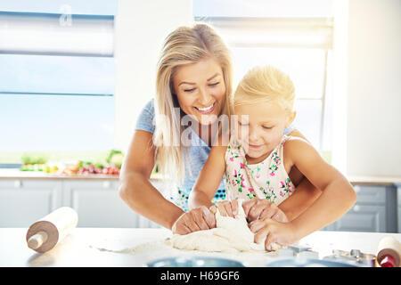 Liebevolle junge Mutter ihrer Tochter zu backen, als sie gemeinsam am Küchentisch stand kneten den Teig für Cookies - Stockfoto