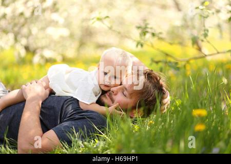 Ein niedliche einjährige Baby Mädchen ist ihr jungen Vater umarmt, wie sie in einem blühenden Baum Apfelplantage - Stockfoto