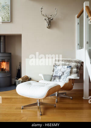 Eine Ikonische Eames Style Leder Sessel U0026 Hocker In Einem Komfortablen  Wohnzimmer Mit Holzofen   Stockfoto