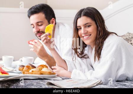 Porträt des Paares zusammen frühstücken im Bett im Hotelzimmer hautnah. Paar Bademäntel tragen. - Stockfoto