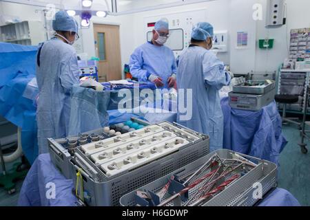 Medizinischem Personal in einem Krankenhaus-OP bei einer Knie-Ersatz-Operation. Bohrer und Ausrüstung stehen im - Stockfoto