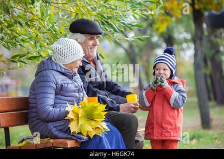 Älteres Paar und Enkel trinken heißen Tee im Herbst park - Stockfoto