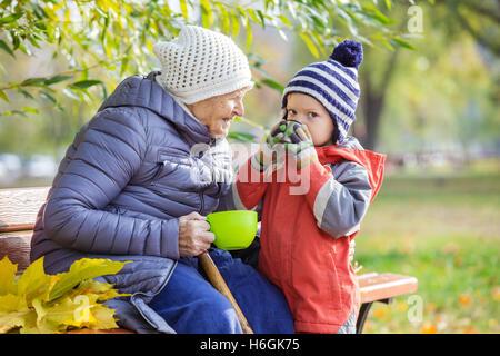 Ältere Frau und ihr Urenkel trinken heißen Tee im Herbst park - Stockfoto