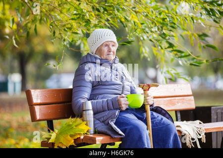 Ältere Frau trinken heißen Tee im Herbst park - Stockfoto