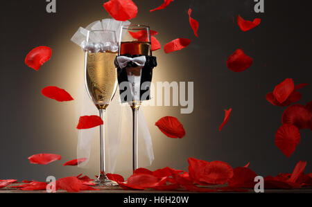 Zwei schöne dekoriert Sektgläser für Brautpaar, umgeben von roten Rosenblüten - Stockfoto