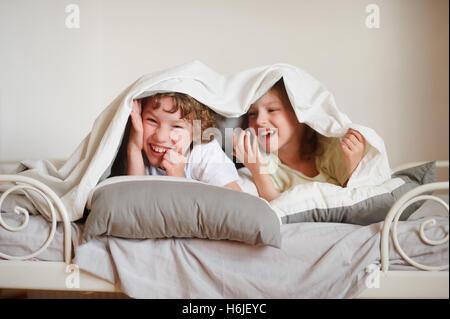 Kleinen Bruder und Schwester machte eine Anspielung auf dem Bett im Schlafzimmer. Kinder schauen unter der Decke, - Stockfoto
