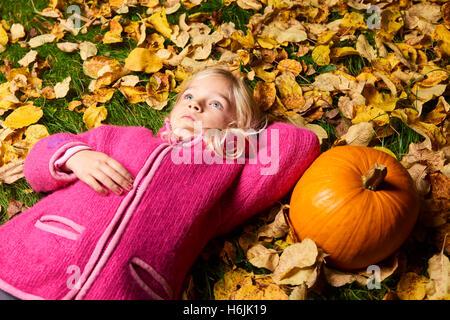 Kind süße blonde Mädchen liegen im Herbst Blätter mit Kürbis. - Stockfoto