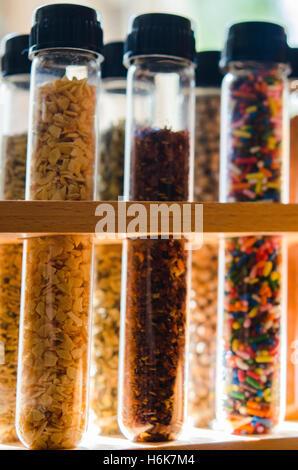 Gewürze und Zucker Streusel im Reagenzglas mit beleuchteten Hintergrund - Stockfoto