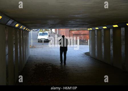 Junger Mann zu Fuß in Unterführung Stadtsilhouette Glasgow, Schottland, Großbritannien - Stockfoto