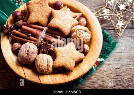 Rustikale Weihnachts-Dekoration mit Lebkuchen, Nüssen und weihnachtlichen Gewürzen über hölzerne Hintergrund mit - Stockfoto
