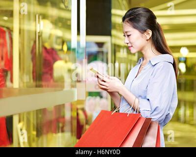 junge asiatische Frau, die mit Handy beim shopping im Einkaufszentrum oder Kaufhaus - Stockfoto