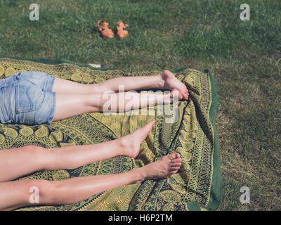 Die Beine der beiden jungen Frauen sind, entspannen Sie sich auf dem Rasen außerhalb an einem sonnigen Tag - Stockfoto