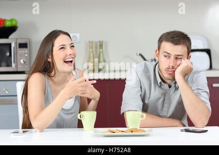 Gelangweilt Ehemann seine Frau beim Frühstück in der Küche zu Hause reden zu hören - Stockfoto