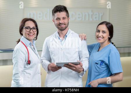 Drei Ärzte mit einem Tablet in helles Büro - Stockfoto