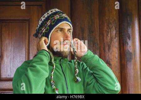 Porträt eines Hipster eine gestrickte Wollmütze aufsetzen - Stockfoto