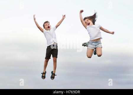 Jungen und Mädchen in die Luft springen und schreien - Stockfoto