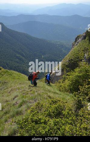 Paar absteigend einen Berggipfel mit einer Landschaft im Hintergrund der FSME - Stockfoto