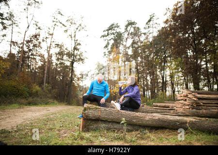 Senior Läufer sitzt auf hölzernen Maschinenbordbüchern, ruhen, Trinkwasser. - Stockfoto