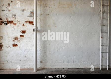 Bemalte Mauer mit Pfeife und Leiter und alten Steinboden - Stockfoto