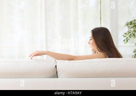 Traurige Frau sitzen auf einer Couch fehlt ihrem verlorenen Mann berühren den leeren Platz zu Hause - Stockfoto