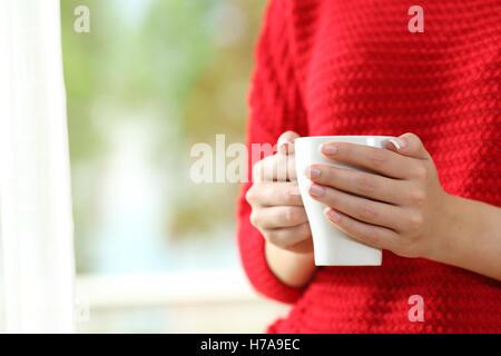 Nahaufnahme einer Frau mit roter Pullover mit Händen hält eine Kaffeetasse neben ein Fenster mit einem grünen Hintergrund - Stockfoto