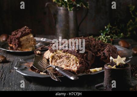 In Scheiben geschnitten hausgemachte Schokolade Yule Bûche mit Kastanien Creme auf Vintage Platte mit Gabeln, Schoko - Stockfoto