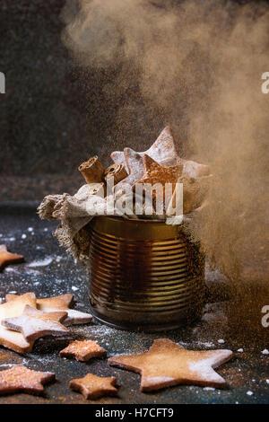 Hausgemachte Sternform Zucker Spritzgebäck mit Zucker und Zimt bestreuen Pulver in alten Blechdose Sackleinen Lappen - Stockfoto