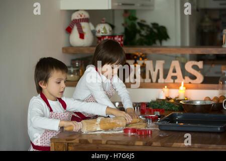 Zwei süße Kinder, junge Brüder, Lebkuchen zu Weihnachten Backen zu Hause vorbereiten - Stockfoto
