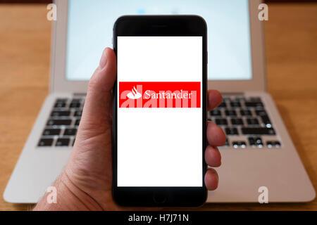 Mit iPhone Smartphone zum Logo der Santander Bank anzeigen - Stockfoto
