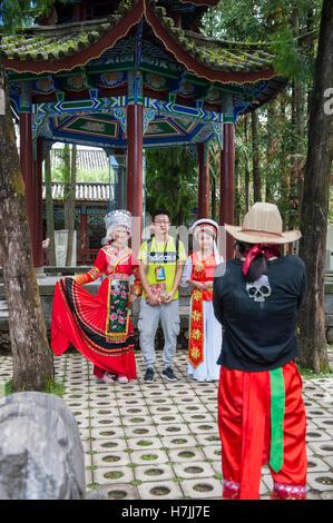 Touristen zahlen mit Frauen zu posieren in Bai Minderheit Kostüme in einem Museum in Dali, einem alten Bai Stadt - Stockfoto