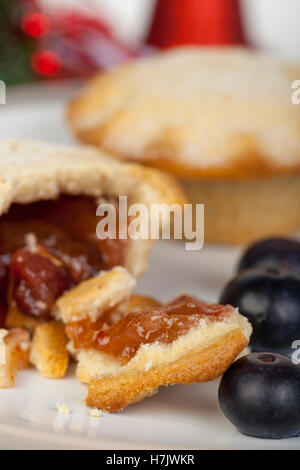 Nahaufnahme der Porträtaufnahme von einem Teil gegessen Mince Pie und Heidelbeeren zu Weihnachten - Stockfoto